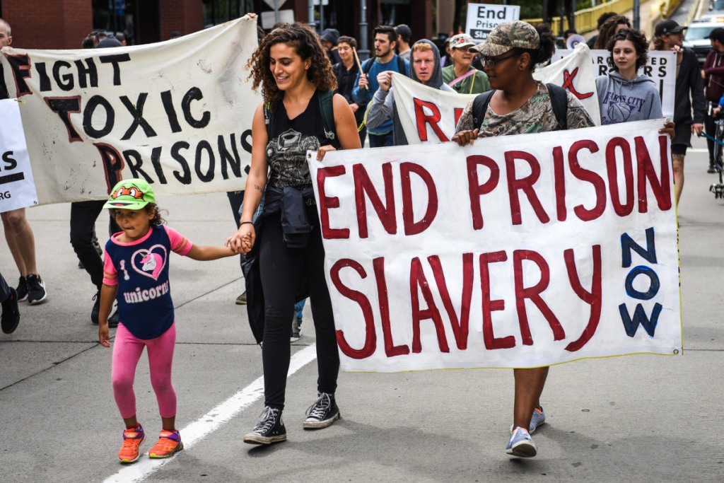 """Two adults and a child march during a protest, with banners reading """"Fight Toxic Prisons"""" and """"End Prison Slavery Now."""""""