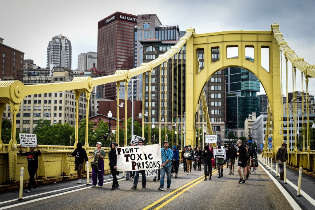 """A protest march crosses a bridge, carrying a banner that reads, """"Fight Toxic Prisons."""""""